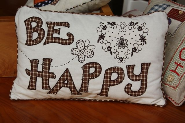 """BE HAPPY"" cushion - embroidered and appliquéd detailing in beige and chocolate browns – 21cm x 36cm"