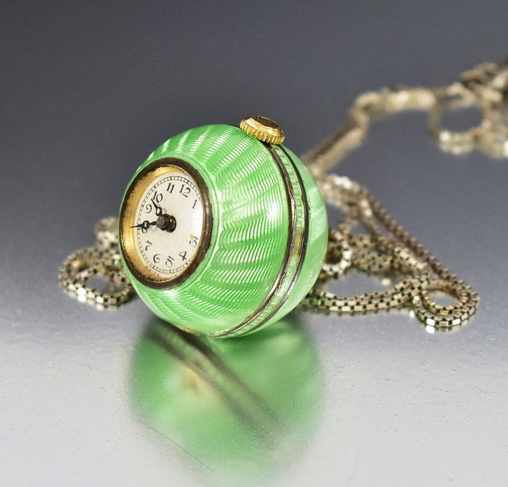 This Liema guilloche enamel ball pocket watch necklace hails from the Art Deco era, circa 1920s. Rendered in a 935 silver gold ore, the 15 jeweled movement watch has a lovely lime green enamel case wi