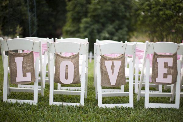 Sacs de jute grand format suspendus aux chaises décorés chacun des lettres formant le mot LOVE
