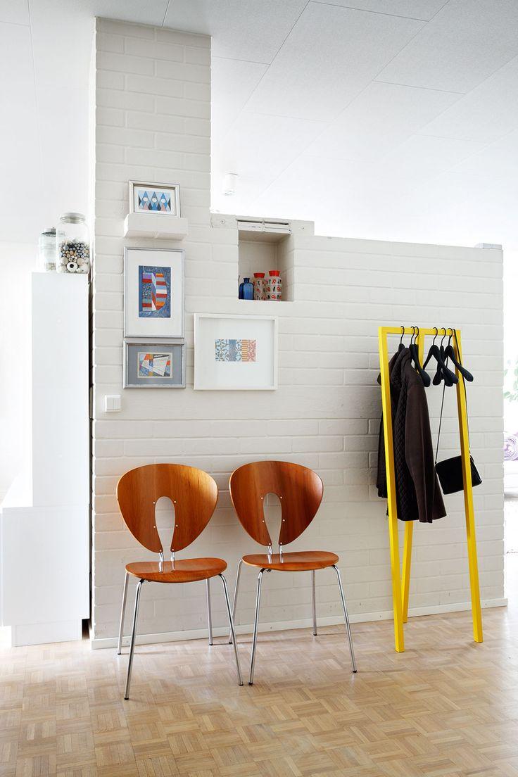 Stuan Globus-tuolit ja Hayn sitruunankeltainen Loop-naulakko raikastavat takan takaseinän muurausta. Takan kolossa on Marja-Leenan lapsuudenkodista saadut 1930- luvun käsinmaalatut lasimaljakot. Maalaukset ovat Juhanin 1990-luvun tuotantoa.