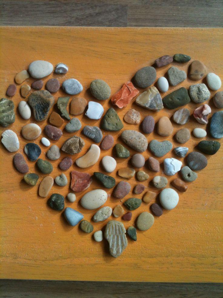 Zoek mooie stenen op vakantie en plak ze met een lijmpistool op een geschilderde houten plank.