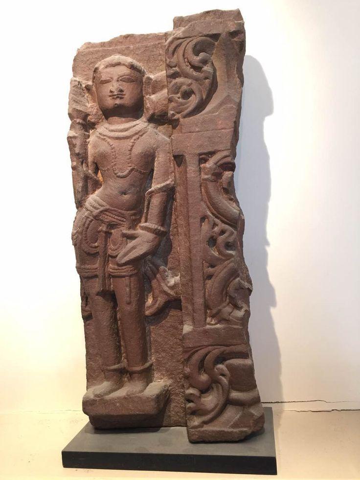 Partie de frise de temple illustrée d'une apsara en tribanga vêtu d'un dhoti et paré de joyaux. Pierre grès rose. Inde. 10 ème à 12 ème siècle. Ht 54cm x larg 24 cm