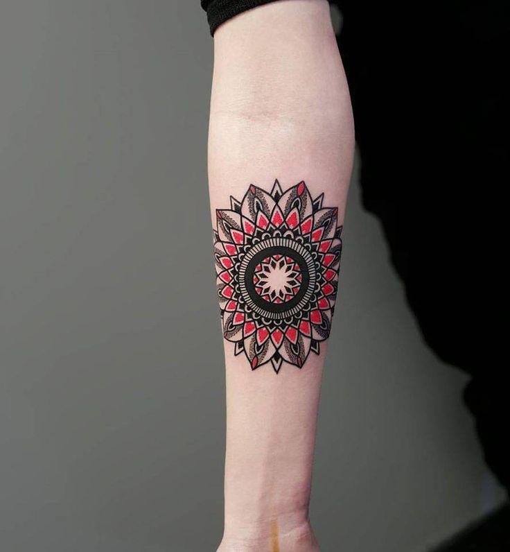 Mandala tattoo on the right inner forearm.