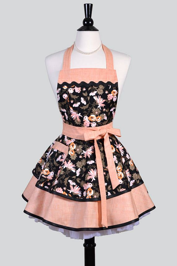 Ruffled Retro Apron in a flirty tangerine, persimmon, orange and black floral. A womans vintage style pinup kitchen apron with pockets that is ideal to personalize or monogram for gift giving or for yourself. A full double layered skirt with a single lined pocket is perfect for stashing your phone. This apron is deal for custom embroidery and personalization.  Details: ~ 100% Cotton, Machine Washable ~ One size fits most ~ Length: 27, Waistband: 26 ~ Lined Bodice, Waistband and Pocket(s)  We…