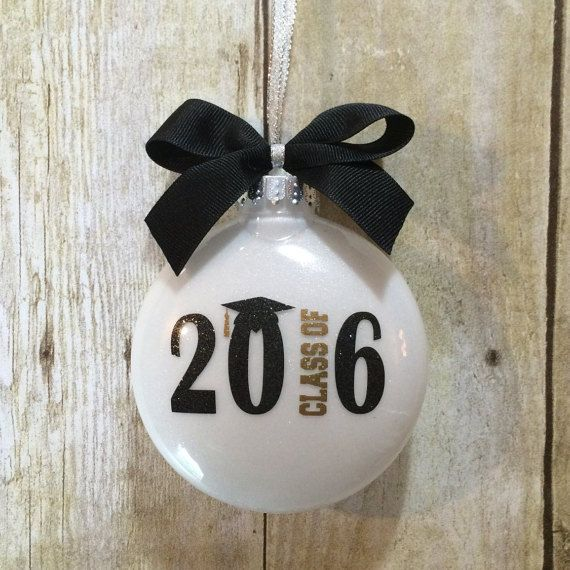 This special Graduation Ornament features a modern class of 2016 logo in black and gold glitter vinyl, a sparkly white glitter background, and is topped with a black grosgrain ribbon bow. The back of the ornament can be personalized with a first name and/or date and/or school initials making it a cherished graduation gift or keepsake. LISTING INCLUDES: • (1) Graduation Ornament FEATURES: • 4 inch plastic disc shaped ornament (m&m shaped) • Shatterproof plastic • White glitter interior…