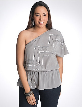Flaunt your sexy, sparkling personality in this stunning one shoulder top with sequins & beads zig-zagging from shoulder to hem. Alluring asymmetric silhouette features one short sleeve and an elastic waist to show off your shape. Hot date or girl's night out, here you come! lanebryant.com