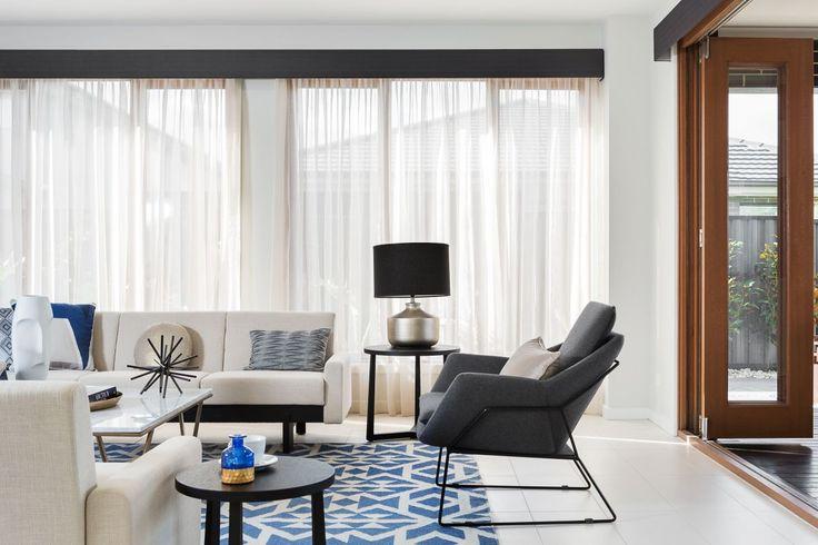 Dark blue coloured pelmet with cream coloured sheer curtains…
