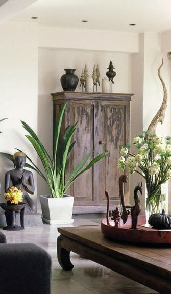 Dark wooden furniture with Asian inspired ornaments add a subtle global look to your home. Add a final touch with greenery. Great for living rooms and dining rooms.