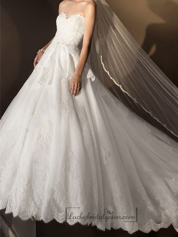 This strapless ball gown wedding dress features beautiful lace throughout. The gently pleated tiered skirt floats light as air and features floral lace motifs throughout the glamorous ball gown skirt.