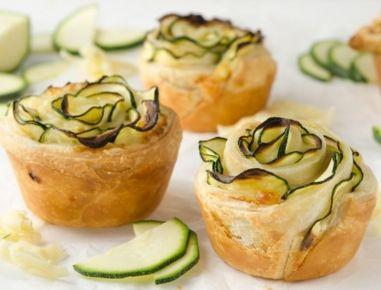 Für die Zucchini-Käse-Rosen die Zucchini waschen und einmal der Länge nach durchschneiden. Eine Hälfte mit der Schnittfläche auf ein Brett legen
