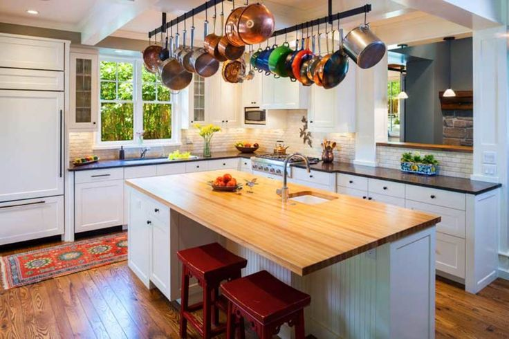The kitchen beyond features granite and maple countertops. Casual (and practical) pot racks were built for the space.