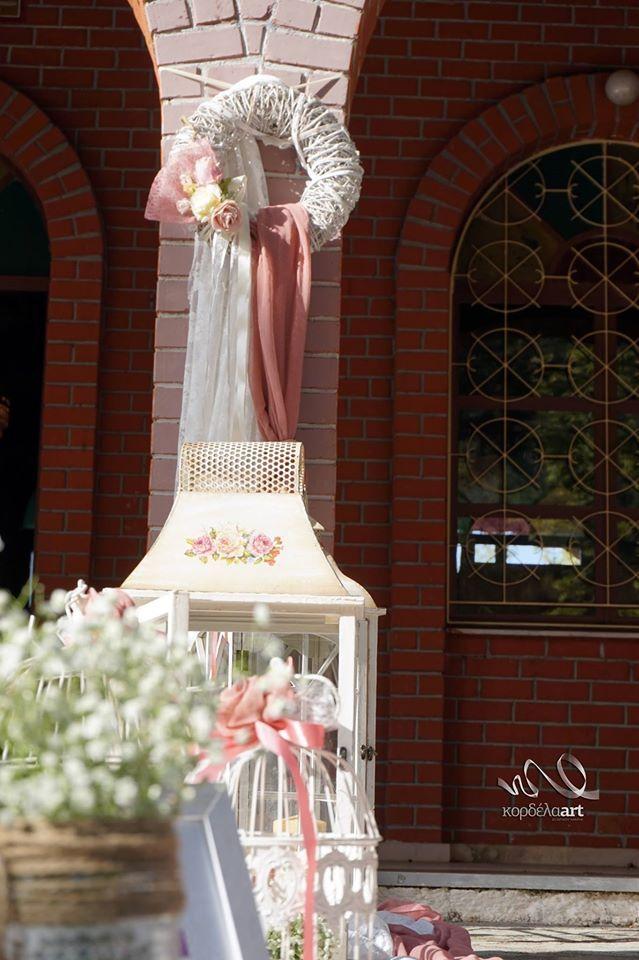 Ρομαντική διακόσμηση εκκλησιάς με μεταλλικά φανάρια και ξύλινα στεφάνια με φυσικά μπουκέτα