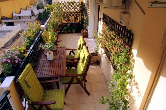 Windbreaks for balcony. Warm wooden slates supporting healthy green foliage. Comfortable armchairs with green cushions. Ideal for late afternoon drinks with friends.