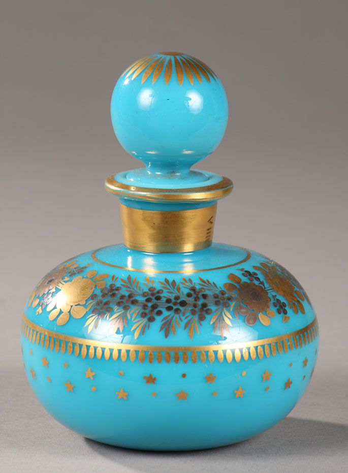 Charles X perfume bottle in turquoise opaline decorated by Jean-Baptiste Desvignes - Small perfume bottle in turquoise opaline with a ball-shaped stopper. Golden stripes, stylized foliage, and little stars surround a gold and dark blue wreath of roses, anemones, and forget-me-nots. Golden bands adorn the neck, and the top of the stopper is embellished with a rosette and petals.  Circa 1820