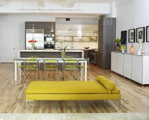 This modern kitchen space uses chartreuse as an accent color, this time with furniture. The interesting thing about this space is the blend of finishes: hickory-tone floors, high-gloss white, charcoal gray cabinets and frosted glass details.