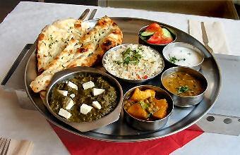 Vegetarische gerechten (van links naar rechts)   Saag Paneer Indiase kaas met spinazie  Alu Matter aardappelen en groene erwten  Dahl Indiase gele linzensoep  Reita bijgerecht  Rauwkorst bijgerecht  Rijst (midden grote schaal)