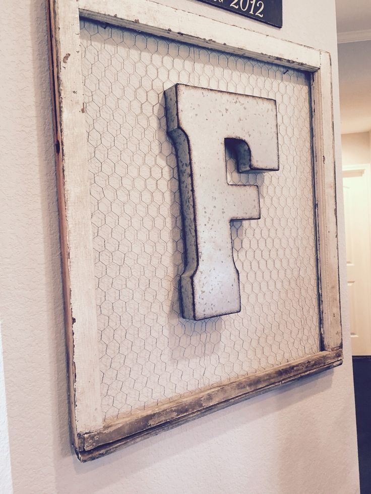 Old window frame with glass removed, chicken wire, metal letter