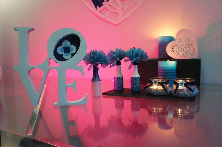 Detalles perfectos para decorar la mesa del día de los enamorados, con porta-fotos con la palabra LOVE, jarrones decorados con purpurina y velas en tonos azules