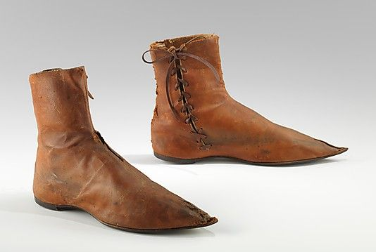 Boots, 1790-1820, UK. The general construction and appearance resembles shoes of the early 1800s. Although the size suggests they were made for a man, the elongated point toe was stylish for women in the period 1795-1810 but extremely unusual for menswear. Additionally, the side lacing was very uncommon until 1830, and the leather thong shoelace, cut in a curve, is also peculiar.