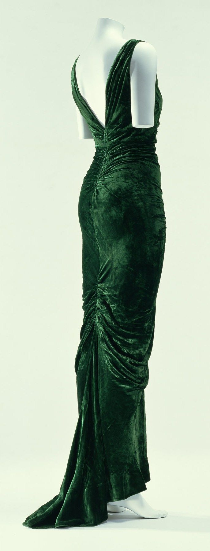 """Evening Dress, Edward Molyneux: autumn/winter 1935, bias-cut velvet. """"This work in the popular mermaid line style of the 1930s, is the triumph of Molyneux's golden age. The bias-cut fabric encases the body closely, and the gathers at the seams create a beautiful drape.  In the 1930s, styles exposing feminine curves returned to fashion. Hair, which was short in the 1920s, became longer again, and previously knee-length skirts became ankle-length..."""""""