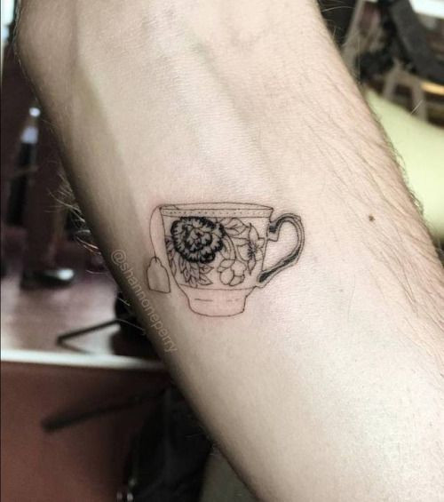 Fine line style tiny teacup tattoo on the left inner forearm. By...