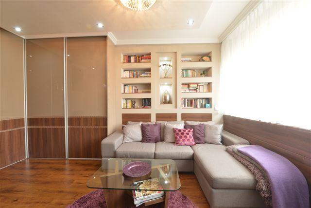 a kanapé mögötti gipszkarton polcok hangsúlyozzák a nappali funkciót a térben