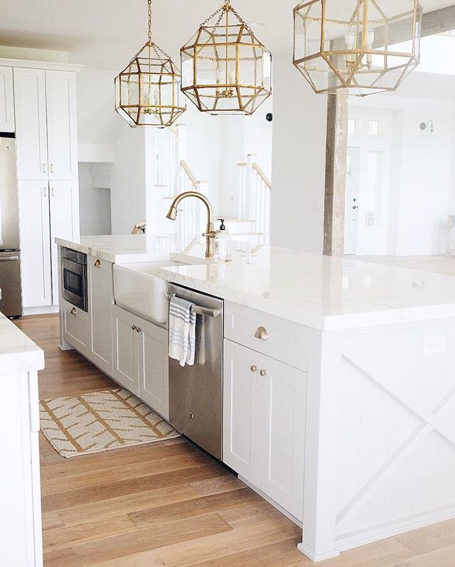 white kitchen + brass pendants + wood floors