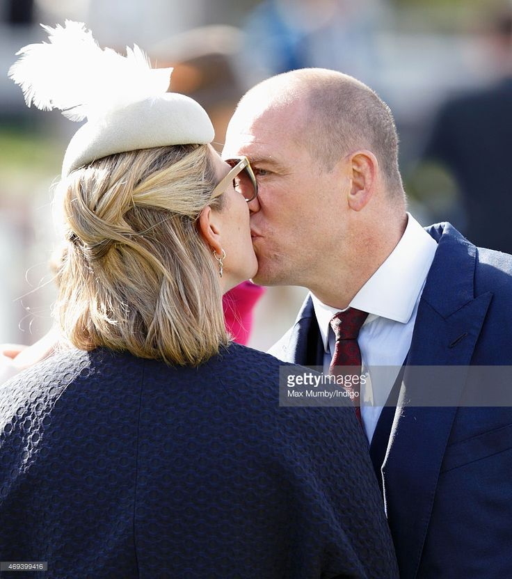 Zara Phillips and Mike Tindall kiss as they attend day 3 'Grand National Day' of the Crabbie's Grand National Festival at Aintree Racecourse on April 11, 2015 in Liverpool, England.