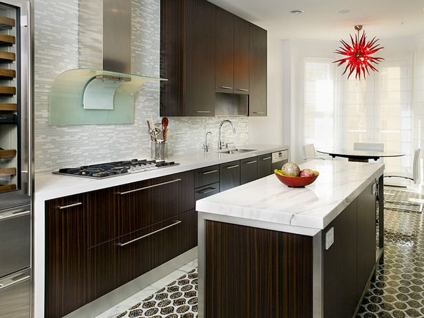 A custom mosaic floor, a custom glass backsplash, sleek cabinetry and a stunning red Murano glass lighting fixture make up this modern timeless kitchen.