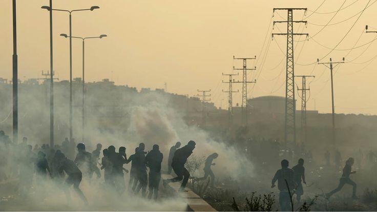 - Palestinos correm de bombas de gás lacrimogêneo na passagem de Erez, Faixa de Gaza.Foto: Mohammed Abed/AFP