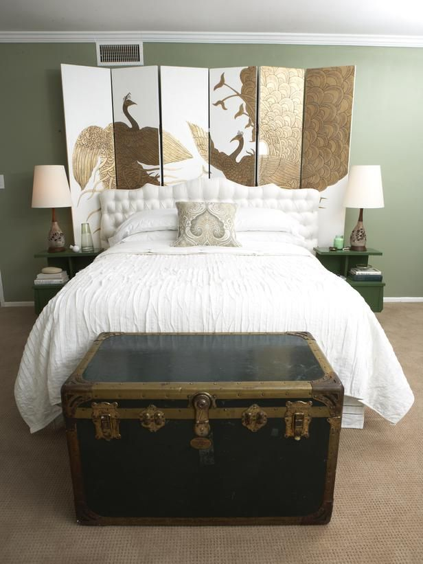 A large steamer trunk acts a footboard and also repeats the gold hue found on the screen at the head of the bed. The bedding is kept clean white to balance out the ornate details. Designer Emily Henderson