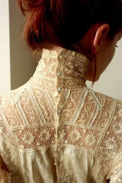high neck, antique lace, buttons down the back.  Beautifully elegant!