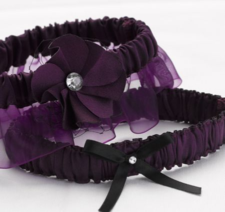 The keepsake garter is covered in purple chiffon, has a layered floral embellishment, purple French netting and a sparkling gem in its center