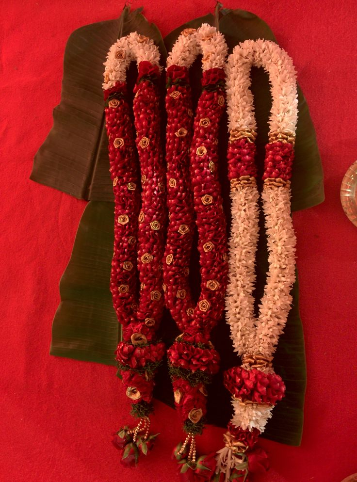 Red themes wedding garland made with red rose petals. #weddinggarlands #indianweddings  From Wishtree Weddings archives