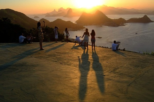People enjoy the view of the Rio de Janeiro bay from Niteroi at sunset in Brazil.