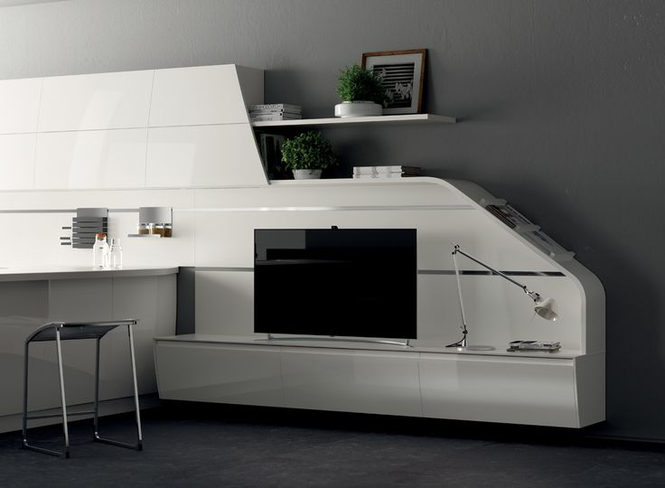 The Slide element, with its sculptural appeal, designs an unprecedented sliding effect which drops from the wall units and embraces the living room base units, repeating the silhouette of the peninsula and end units with tilted doors.