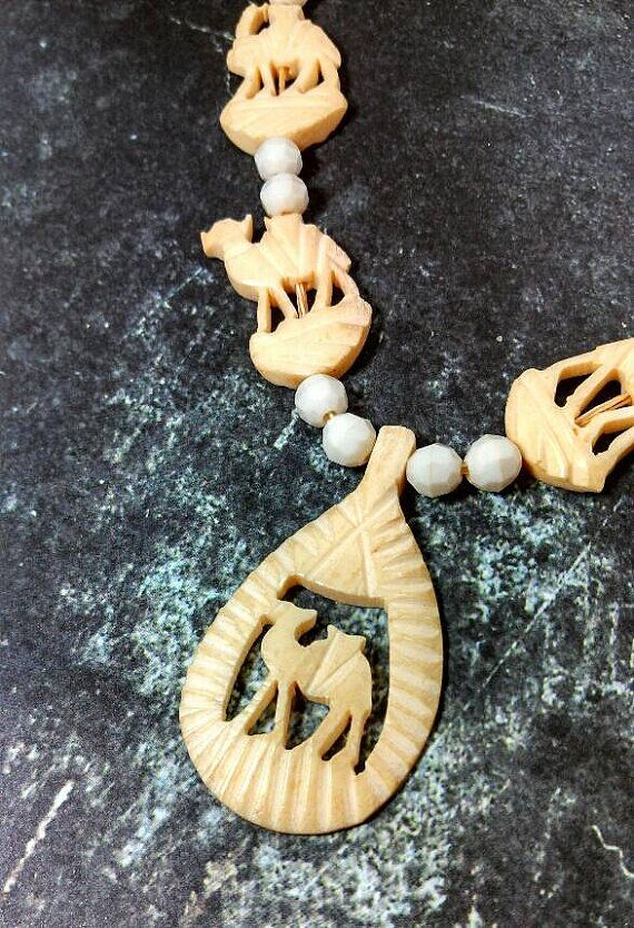 Unique carved Ivory colored resin or plastic Camel necklace. Off white and white beads. Very different and cool