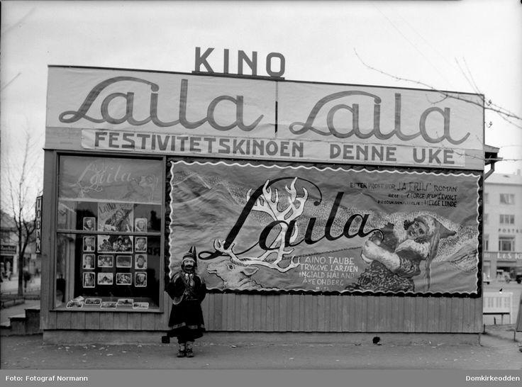 """Kinoreklame på Østre Torg for relanseringen av filmen """"Laila"""" som skulle vises på Festiviteten Kino. For å skape litt publisitet rundt filmen fikk kinosjef Hans Smørsten unggutten Alfred Sakrisvold til å kle seg ut som en av rollefigurene. Disse brakkene ble satt opp etter brannen i posthuskvartalet i 1935 slik at butikkeierne kunne fortsette med sin forretningsdrift. - Domkirkeodden / DigitaltMuseum"""