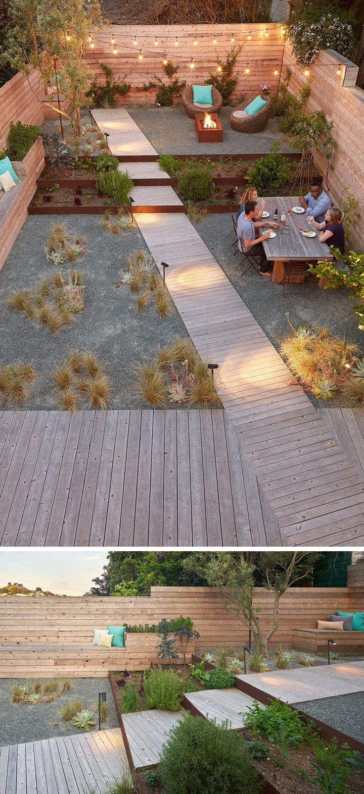 Este quintal totalmente ajardinado tem o espaço dividido em várias seções, como jantar, socializar, e descansar.  Ao longo de um lado do quintal, é um banco de madeira, que quase corre todo o comprimento do espaço.