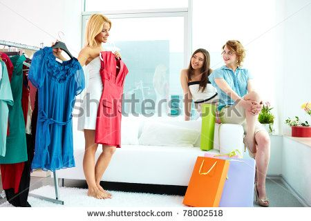 Image of pretty females looking at their friend trying on smart dress while choosing a right one - stock photo