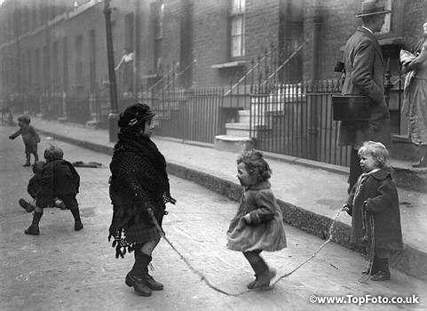 London Slum scenes. Off Louisa Place, Shoreditch, East London. Children skipping in the street.