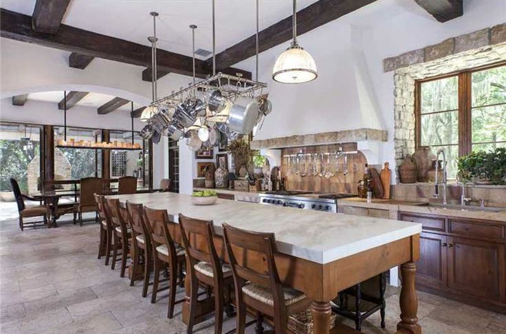 Mediterranean style kitchen with long seating island with marble counter