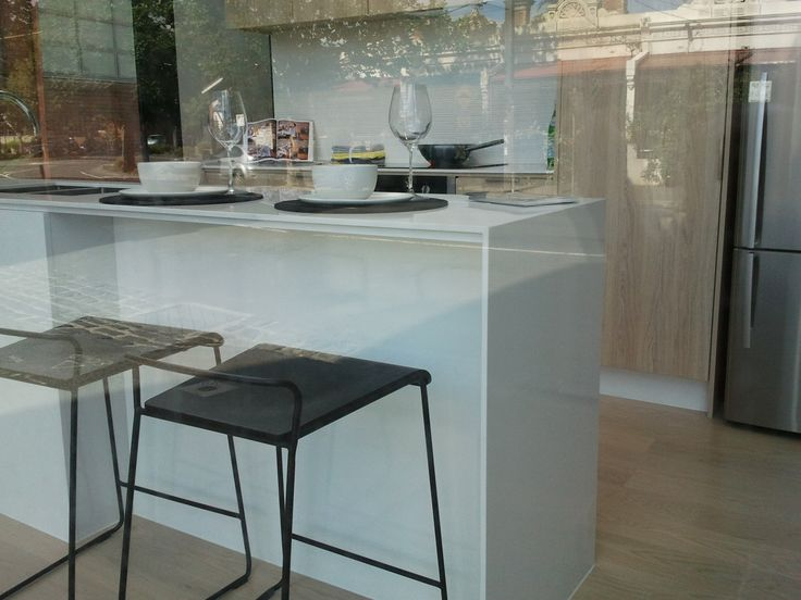 thin, white stone benchtop with birch veneer cabinets