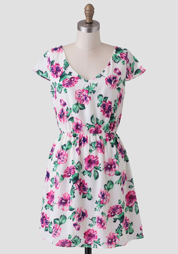 This cream-colored fit-and-flare dress features a stunning saturated floral print in hues of fuchsia, green and purple.