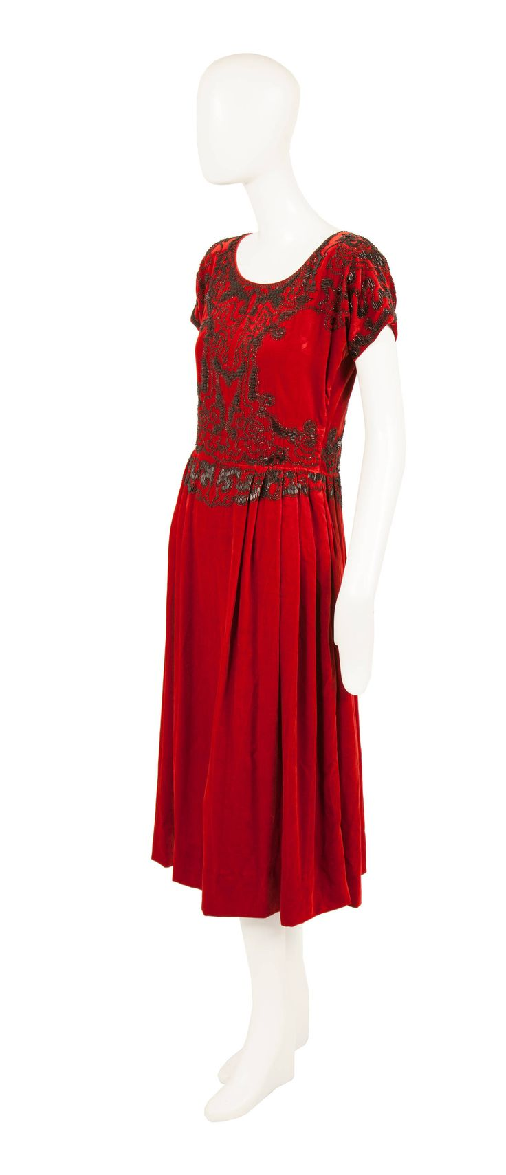 Paul Poiret Haute Couture Red Silk Velvet Dress, circa 1925 ruby red silk velvet, the dress is intricately embroidered with black glass bugle beads on the body and capped sleeves, while the skirt is pleated around the waistline to create a gentle draping.