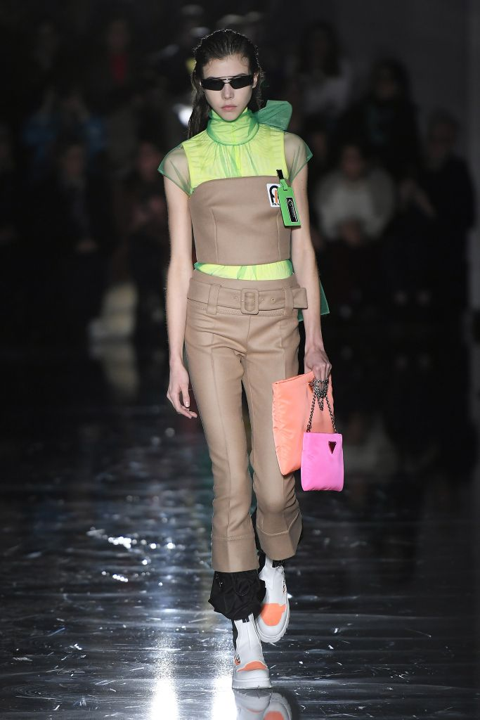 Tan tube top over neon sheer green lining and cropped pants with hot pink and orange clutch bags at Prada Fall 2018 RTW show Milan Fashion Week