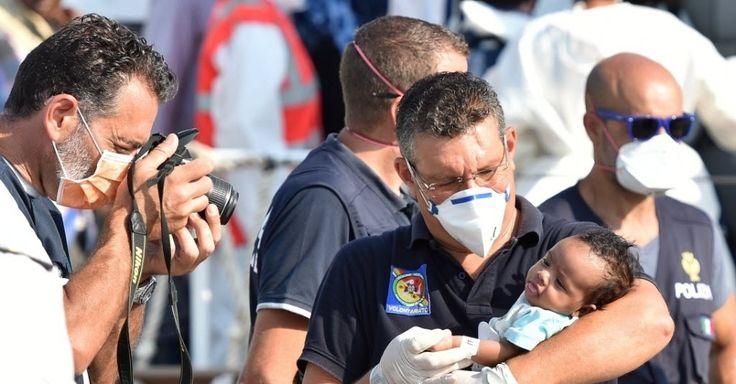 20150807 - Policial italiano tira uma foto de um bebê imigrante retirado de um navio da Guarda Costeira italiana, no porto de Pozzallo, na Sicília, Itália. Na quinta-feira, 381 pessoas foram resgatadas de um barco que afundou na costa da Líbia. PICTURE: Carmelo Imbesi/AP
