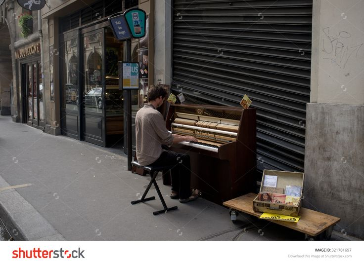 PARIS, FRANCE, AUGUST 3, 2013: in the morning a street musician plays piano near Place des Vosges  in the centre of the french capital.