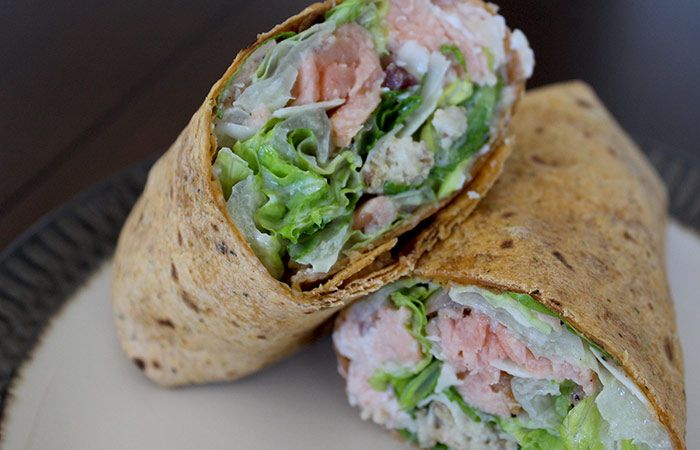 Caesar Salmon Wrap - 1 pound salmon fillet, cut into 1 1/4-inch strips; olive oil; salt and pepper; 4 cups summer romaine lettuce torn into bite-size pieces; ¼ cup Caesar dressing; 2 tablespoons grated Parmesan cheese; ¾ cup croutons; 4 whole-grain wraps. Calories 364