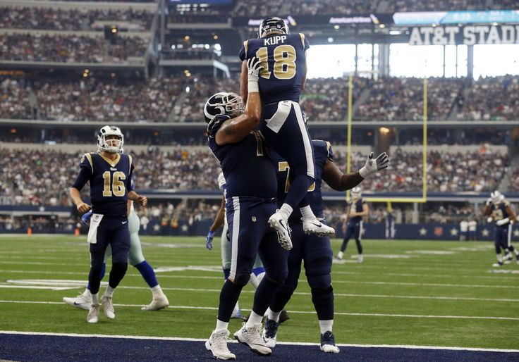 Los Angeles Rams quarterback Jared Goff (16) watches as offensive tackle Robert Havenstein, center, lifts wide receiver Cooper Kupp (18) as the celebrate a touchdown scored by Kupp in the first half of an NFL football game against the Dallas Cowboys on Sunday, Oct. 1, 2017, in Arlington, Texas.